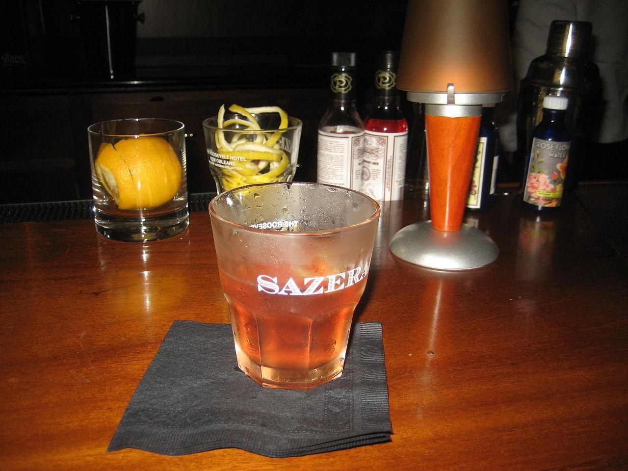 glass full of sazerac on a bar table