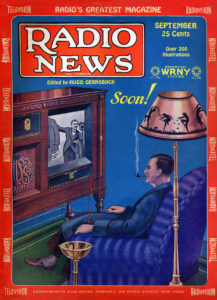 Man watching television on his sofa, smoking a pipe, under a lamp.